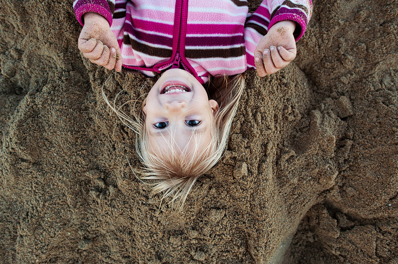 Little girl laying in the sand at Seal Beach.