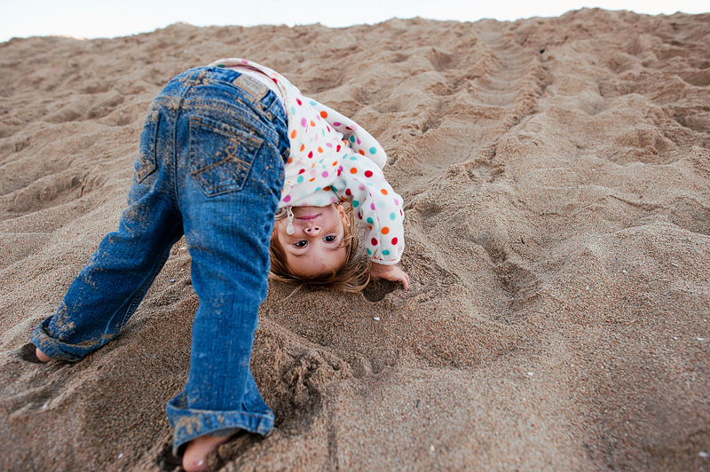 Toddler doing somersaults on the beach.