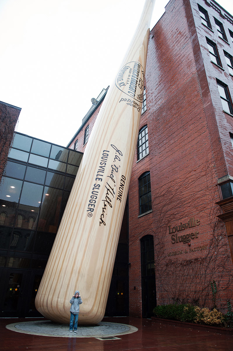 Boy in front of the huge Louisville Slugger bat in Kentucky.