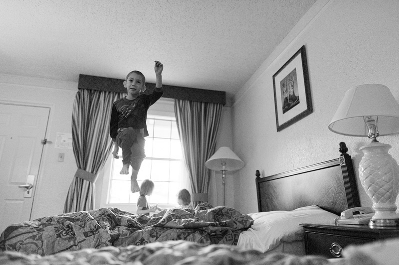 Boy jumping on a hotel bed.