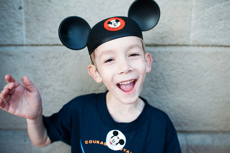 A boy wearing a mickey mouse ears hat and a jedi training academy t shirt.