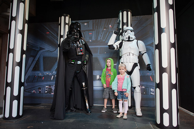 Brother and sister posing with Darth Vader and stormtrooper.