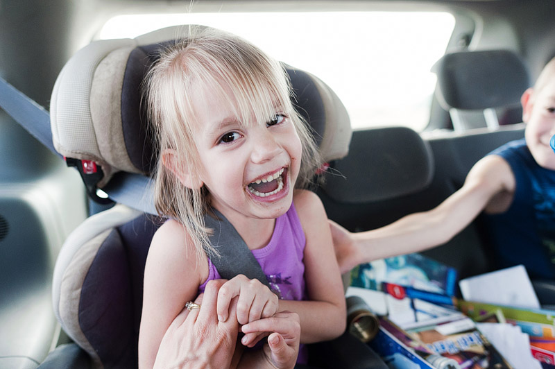 Mom tickling her daughter in the car.