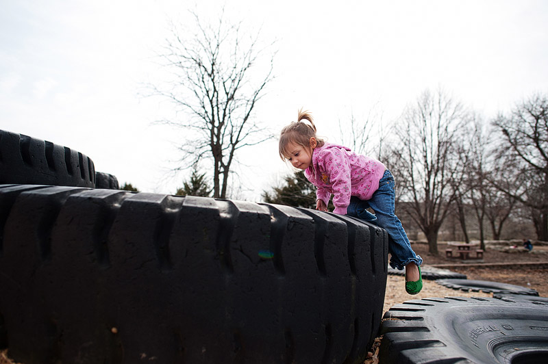 Girl climbing on huge tire in a park in Columbia, MO.