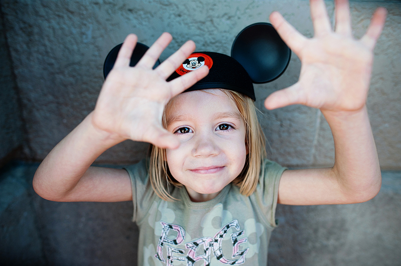 a girl wearing mickey mouse ears at Disney World.