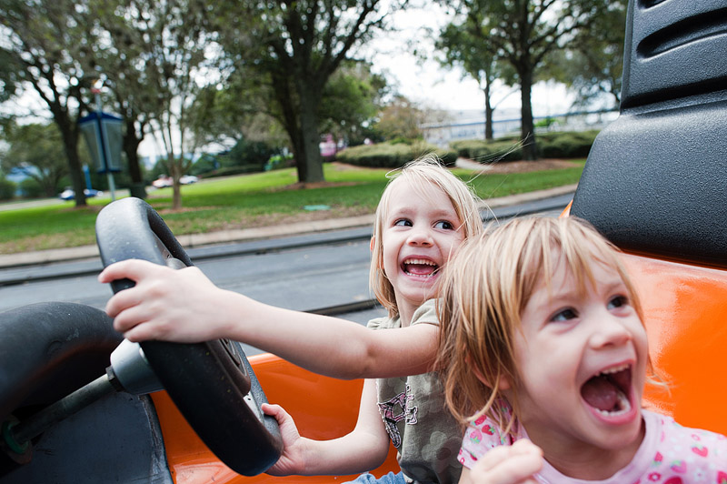 Girls squealing with delight in cars at Disney World's Magic Kingdom.
