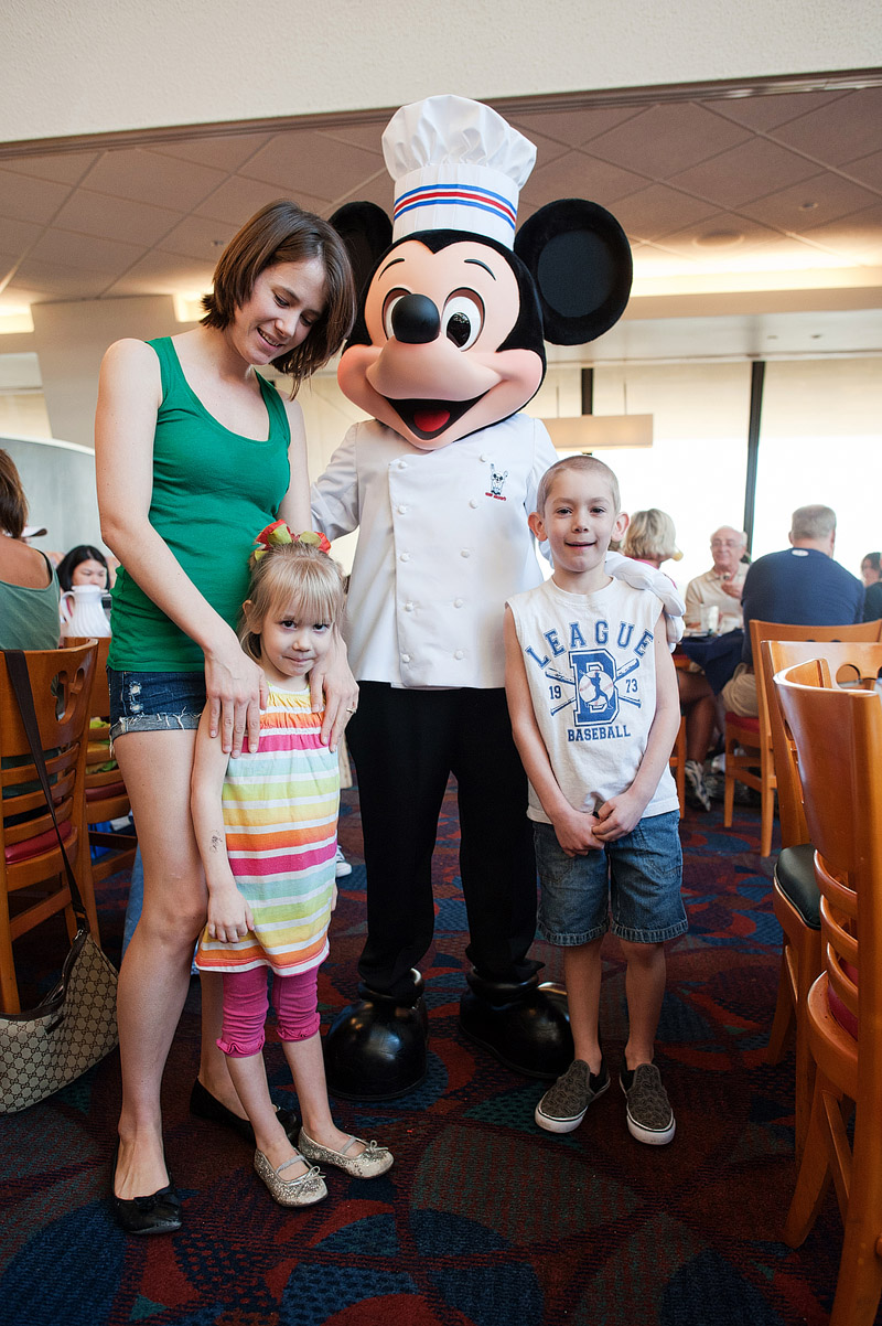 Mom and kids posing with Mickey Mouse at Disney World.