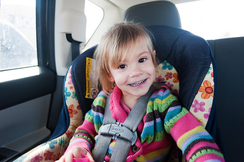 Toddler smiling in her carseat.