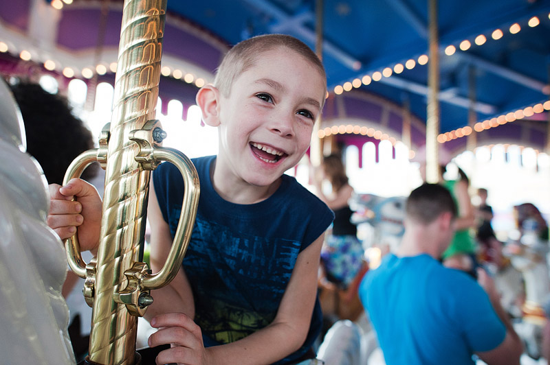 Boy riding the Prince Charming Regal Carousel at Magic Kingdom.