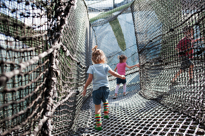 Kids playing on spiderweb playground.