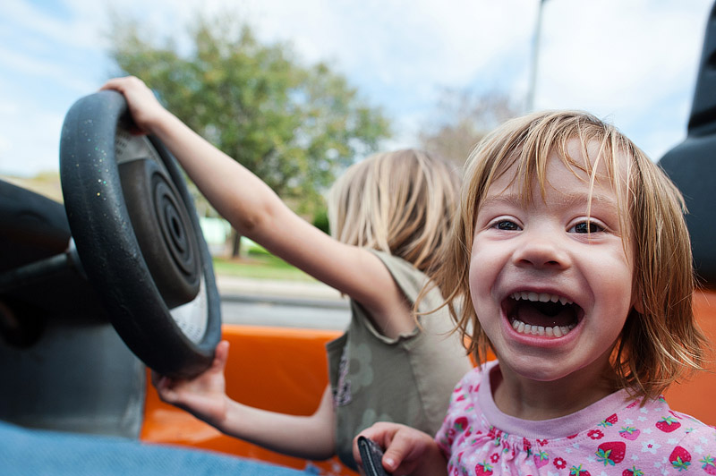 Toddler giggling at Tomorrowland Speedway.