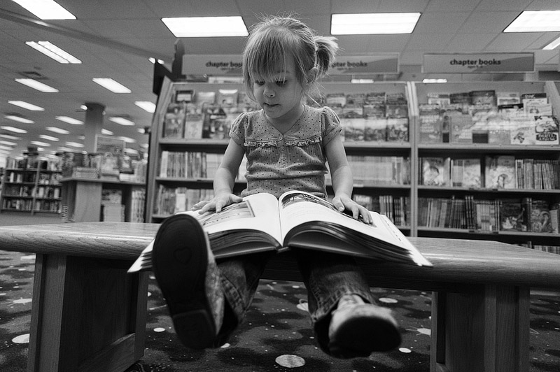 Toddler reading a book at Borders.
