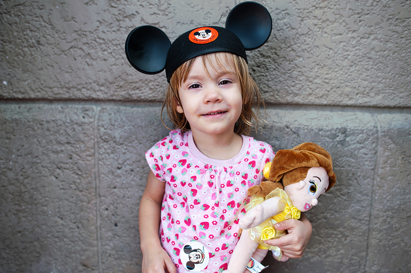 A toddler wearing mickey ears and holding a Belle princess doll.