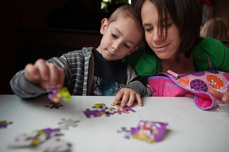 Boy doing a puzzle with his mom while waiting for breakfast.