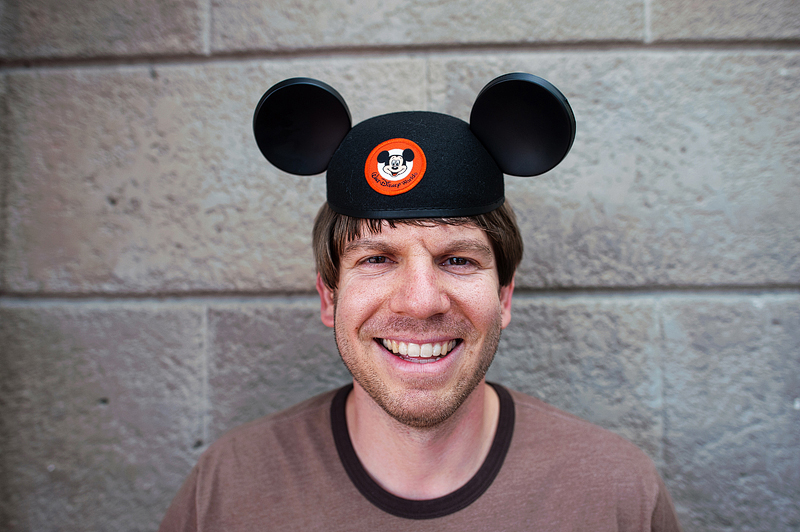 A dad wearing kid sized mickey ears at Disney World.