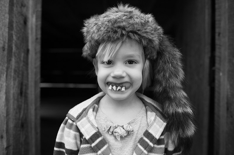 Girl weith a coonskin hat and hillbilly teeth.