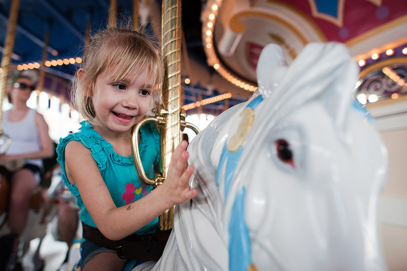 Girl riding a horse on the carousel.