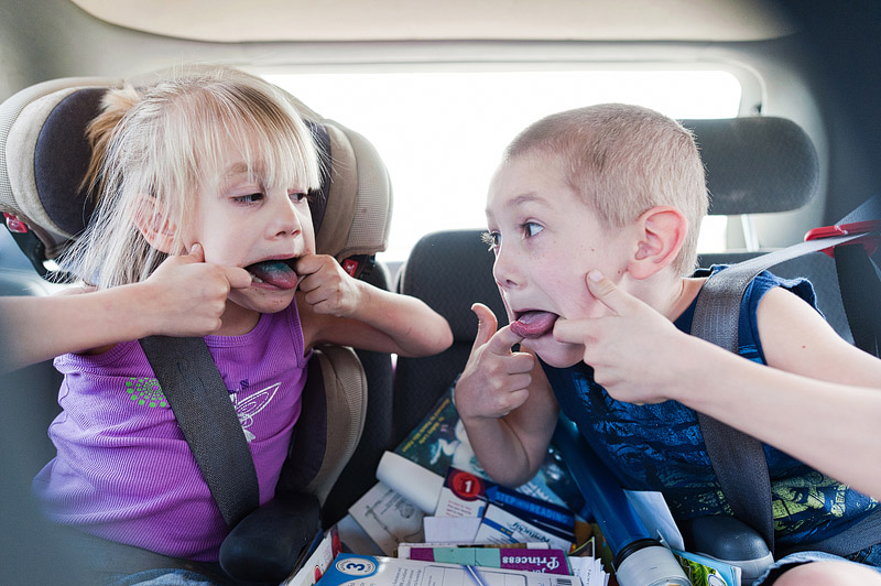 Kids making silly faces in the car.