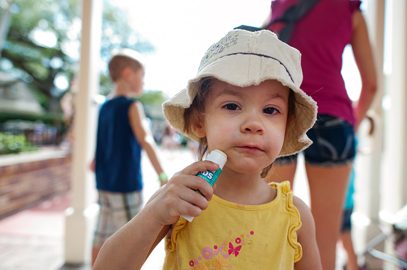 Toddler girl putting on face stick sunscreen.