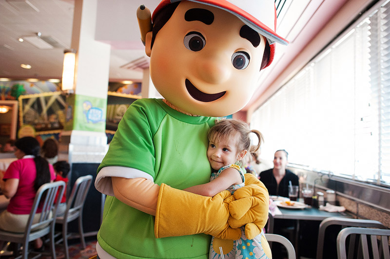Little girl hugging Handy Manny.