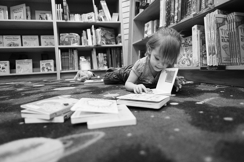 Toddler on the floor at Borders reading books.