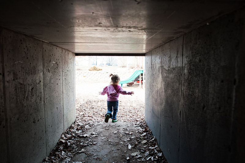 Girl running out of a tunnel.