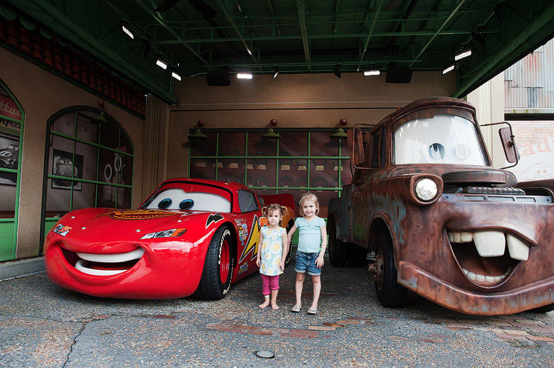 Sisters standing with Lightning McQueen and Mater at Disney's Hollywood Studios.