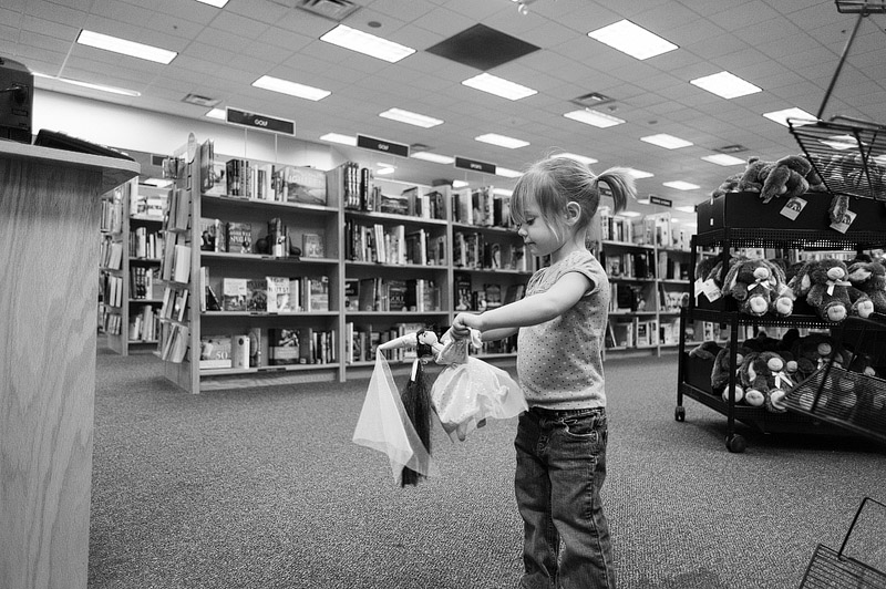 Toddler dancing with a stuffed princess toy at Borders.