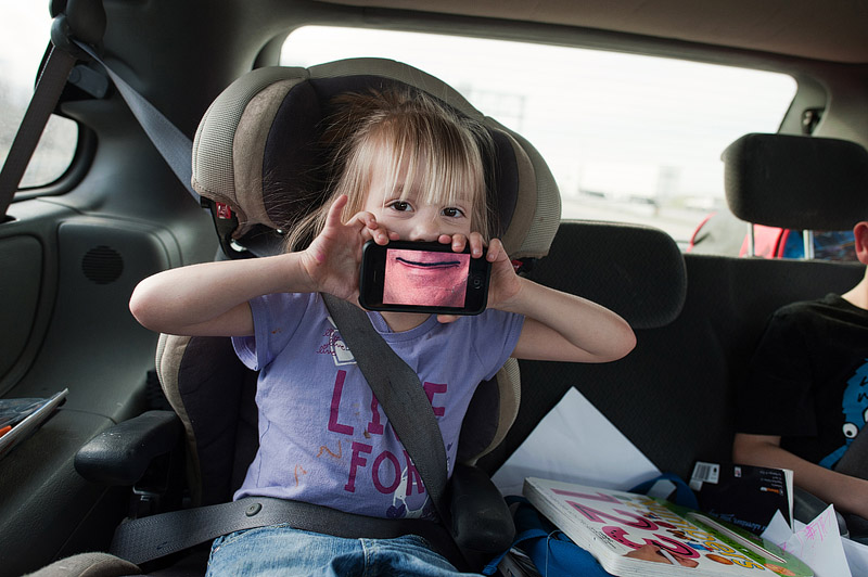 Girl playing with mustache app on an iphone.