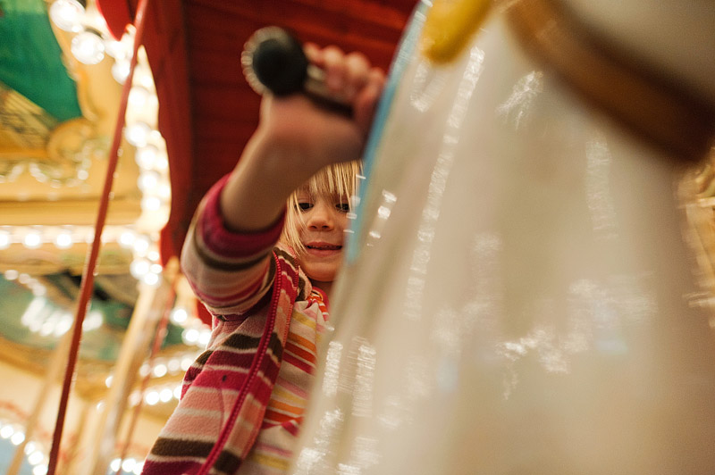 Girl riding a carousel at the mall.