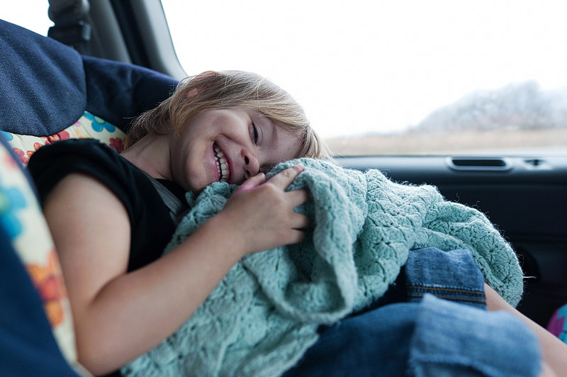 Toddler snuggling her blanket in the car.