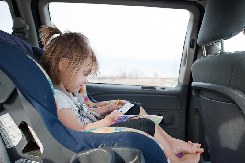Girl coloring in the car.