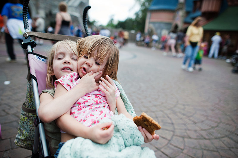 Toddler on her sisters lap in stroller at Magic Kingdom.