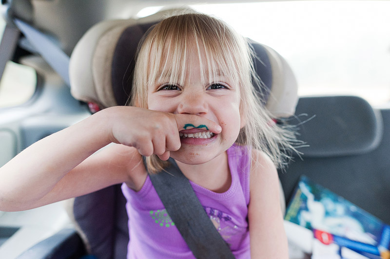 Girl making a silly mustache face with her finger.