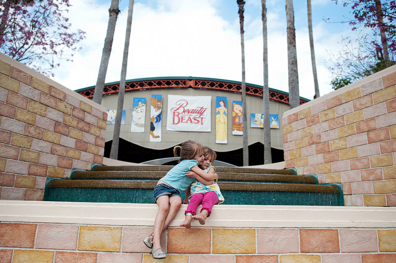 Sisters in front of the Beauty and the Beast stage.