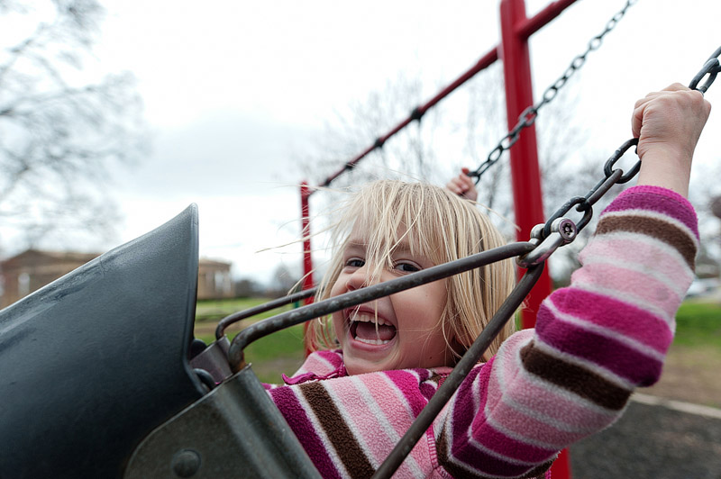 Laughing girl swinging at a playground.
