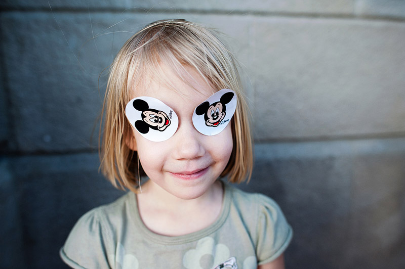 Girl with Mickey stickers on her eyes being silly.