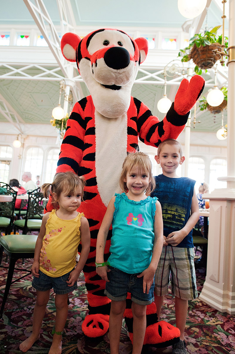 Kids posing with Tigger at the Crystal Palace at Disney's Magic Kingdom.