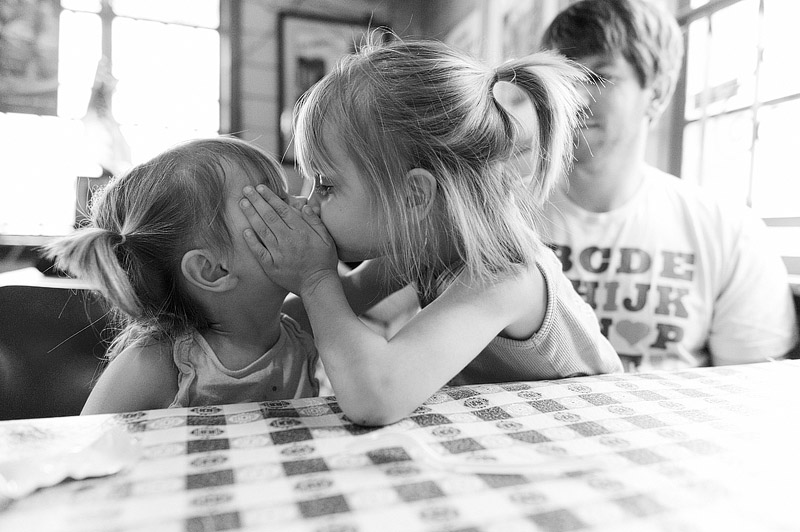 Girl giving her little sister a kiss.