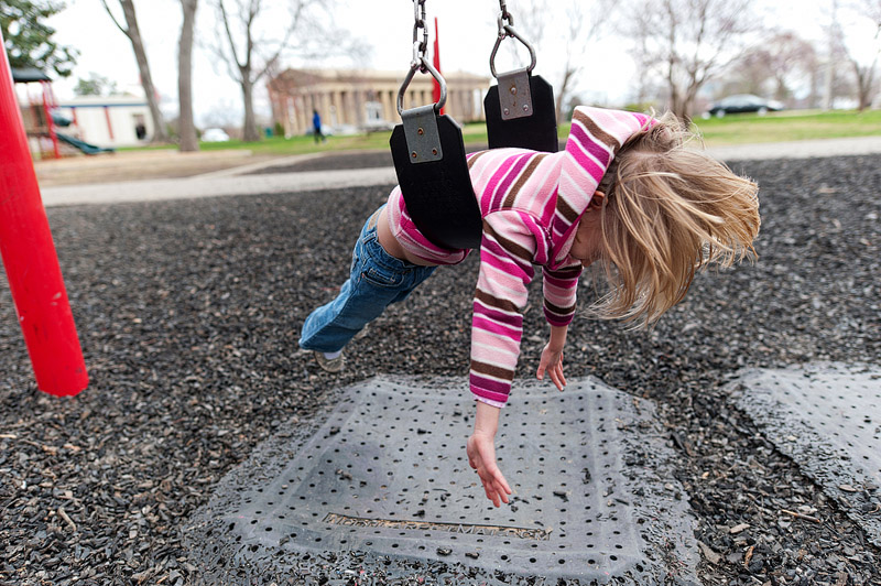 Girl spinning on a swing.