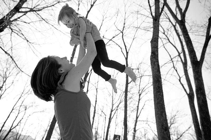 Mom tossing toddler in the air.