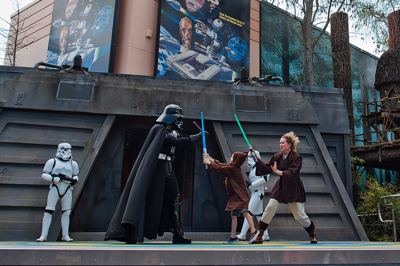 Padawan fights Darth Vader with lightsaber.