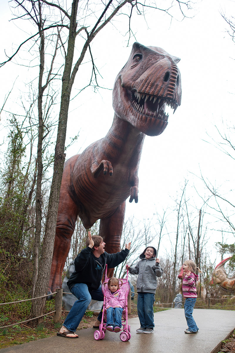 Family pretending to be scared by a T-Rex.