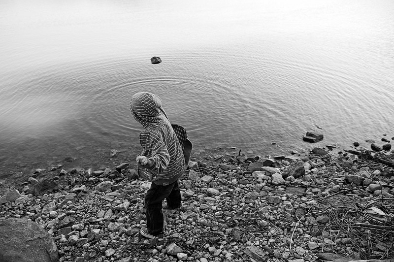 Boy throwing rocks into Parksville Lake in Tennessee.