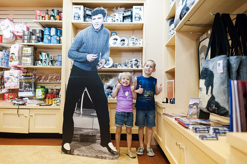 Kids posing with Elvis cardboard cutout.