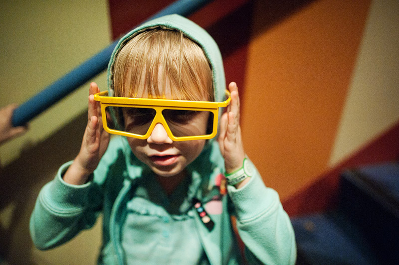 Girl wearing 3D glasses at Toy Story Midway Mania ride at Hollywood Studios.