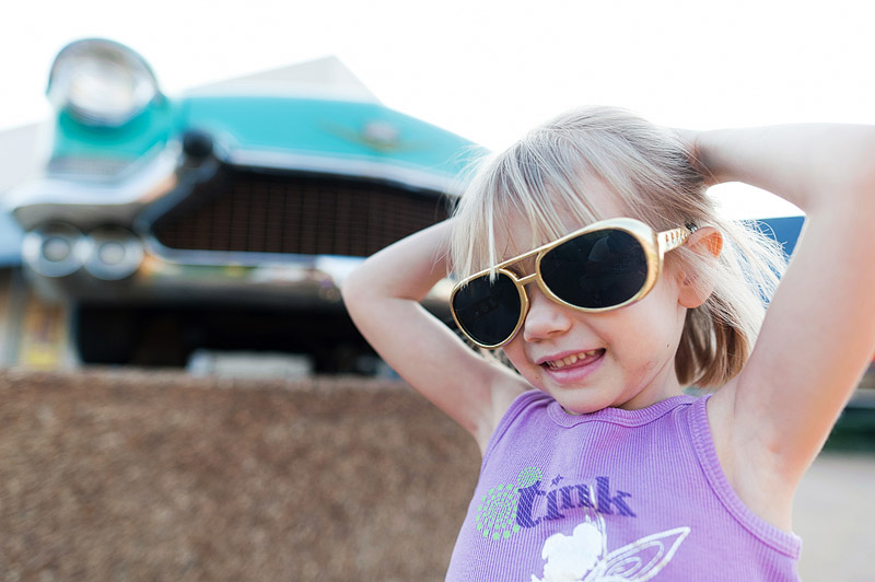 Girl with Elvis glasses on in front of a vintage car at Graceland.