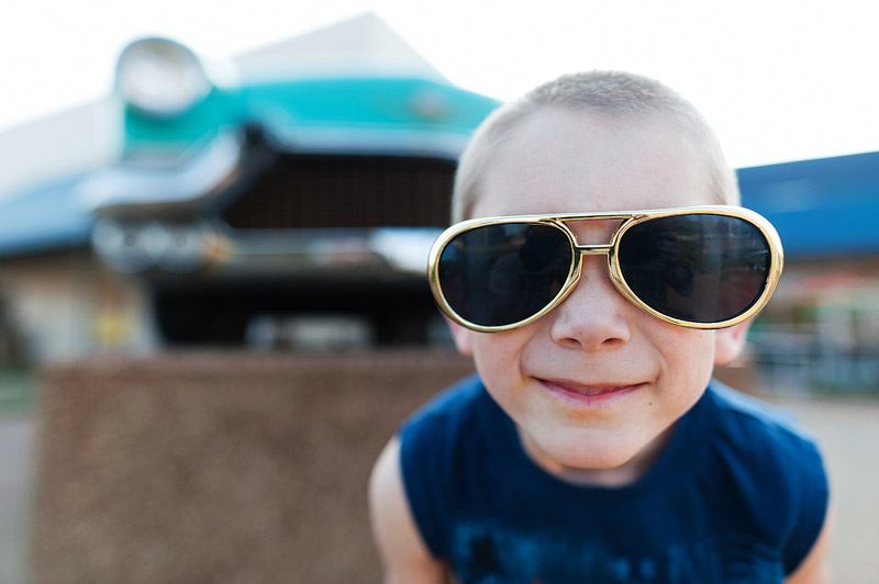 Boy with Elvis glasses on in front of a vintage car at Graceland.