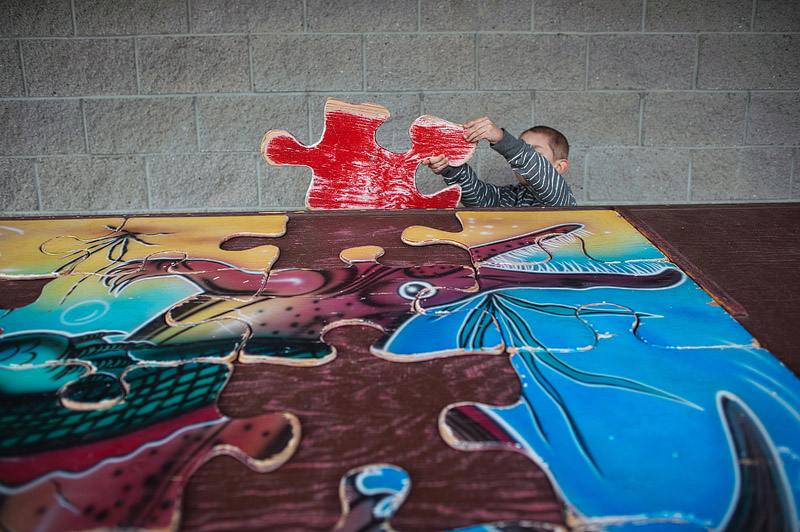 Kid doing a giant dino puzzle.