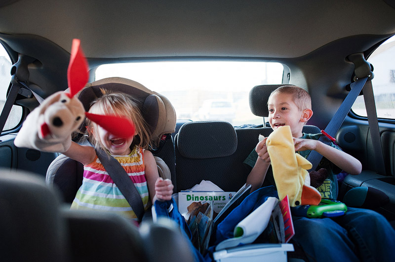 Kids playing with Baby Einstein hand puppets in backseat of Dodge Grand Caravan on a family road trip.